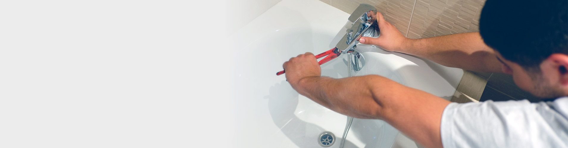 Notre plombier de Lyon réalisant le serrage d'un mitigeur