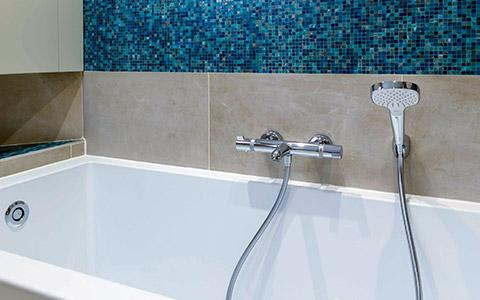 Pose d'une baignoire classique dans une salle de bain contemporaine