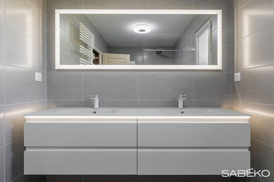 Le lavabo aux lignes épurée trone dans la salle de douche